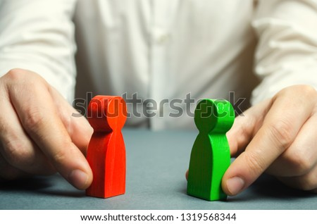 A man holds in his hands the red and green figures of people facing each other. Conflict resolution, conflict of interest. The search for a compromise, mediation in negotiations. Weave intrigue.