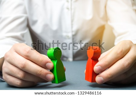 A man holds in his hands the red and green figures of people facing each other. The search for a compromise, mediation in negotiations. Weave intrigue. Conflict resolution, conflict of interest.