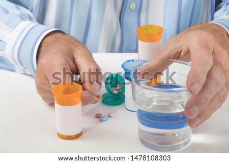 a man holds many pill from many pill bottles in the fingers of one hand and a glass of water in the other hand