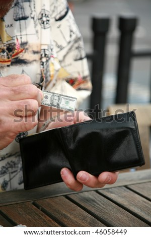 A man holds miniature money representing the shrinking economy