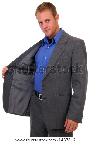 A man holds open his suit jacket