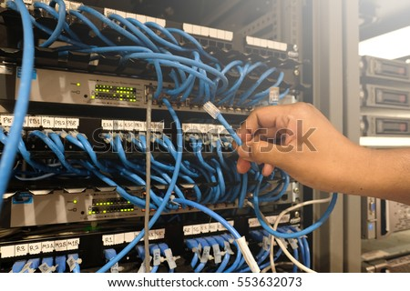 A man holds server cable in Server rack with blue internet patch cord cables connected to black patch panel in server room