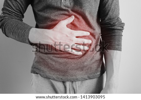 A man holds the stomach. The pain in his chest. Heartburn. Stomach hurts. Sore point highlighted in red. Closeup. Isolated