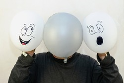 A man holds three balloons in front of his face. Two white balloons with faces painted on them. A gray balloon with no drawing. Opposite hand-drawn emotions. Indoors.