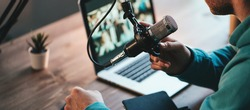 A man host streaming his audio podcast using microphone and laptop at his small broadcast studio, close-up