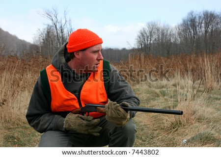 A man hunting with gun in field - stock photo