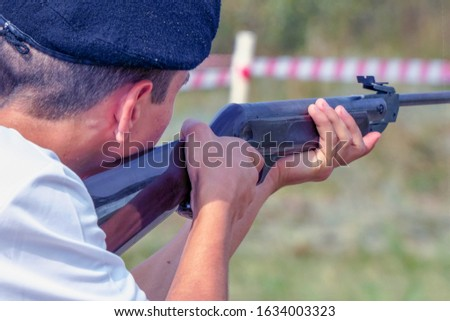 A man in a beret takes aim or shoots with a gun. Back view. Selective focus