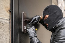 A man in a black balaclava mask opens a locked door with a lock pick. The robber breaks into the house. Robbery of a private house. Criminal concept