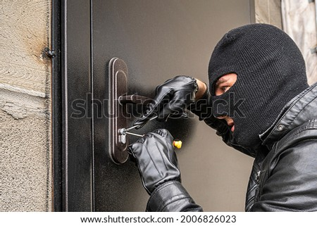 A man in a black balaclava mask opens a locked door with a lock pick. The robber breaks into the house. Robbery of a private house. Criminal concept Foto stock ©