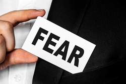 A man in a black business suit lowers or removes from his breast pocket a white business card with the inscription FEAR First Encounter Assault Recon. Business concept