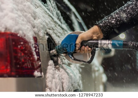 A man in a black coat fills his car at a gas station on a snowy winter evening. Hand holding a blue refueling gun.