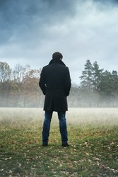 A man in a black coat in foggy weather