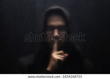 A man in a black hood and glasses gesturing silence. Scary man standing behind a transparent plastic. Concept for threat, violence, danger, menace.  Сток-фото ©