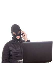 a man in a black mask with a cell phone and a laptop is engaged in Internet fraud