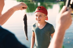 A man in a black T-shirt is holding a fish he has just caught. A boy in a red cap is standing and looking at the catch with delight