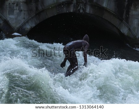 a man in a black wetsuit is in the water under the bridge #1313064140