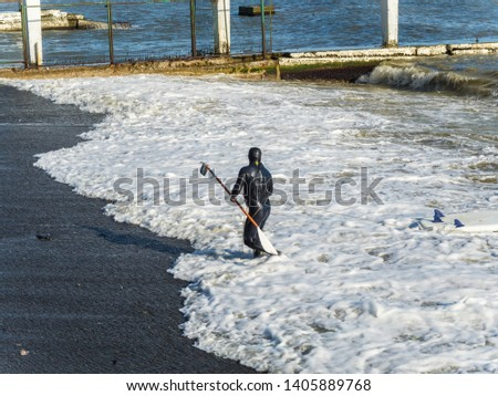 A man in a black wetsuit with a surf #1405889768
