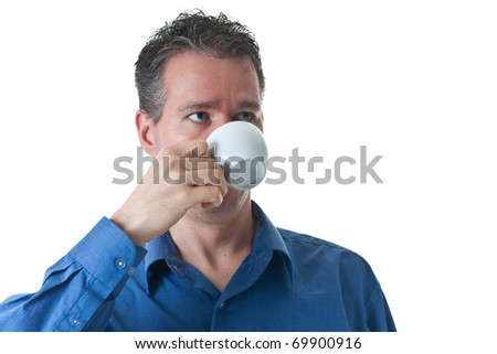 A man in a blue dress shirt, drinking from a small cappuccino / coffee cup, isolated on white.