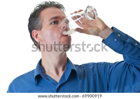 A man in a blue dress shirt, finishing a drink of pop from a glass with ice, isolated on white. - stock photo