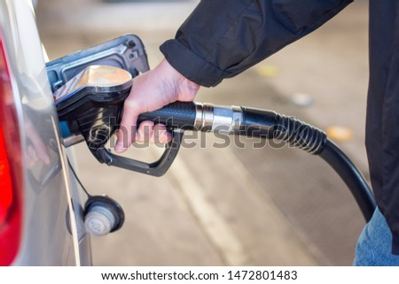 A man in a blue jeans and black coat holding pump filling gasoline. Pumping petrol into the tank. A car refuel on gas station