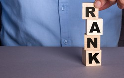 A man in a blue shirt composes the word RANK from wooden cubes vertically
