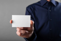 A man in a blue shirt holding a white business card