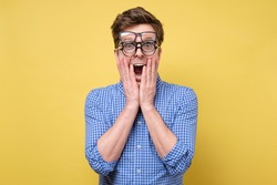 A man in a blue shirt with several glasses for vision is shocked with trouble of choice. Studio shot