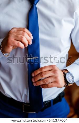 a6fd9e3cc298 A man in a blue suit putting on a tie clip #541377004
