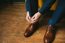 A man in a blue suit ties up shoelaces on brown leather shoes brogues on a wooden parquet background