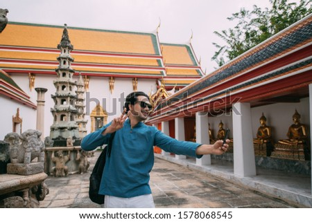 A man in a Buddhist temple takes pictures, takes a selfie on the phone. A young guy in a simple national T-shirt against the background of the sights of the palace makes a photo smartphone.
