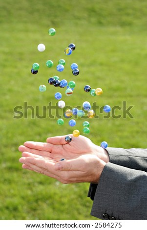 A man in a business suit catching many falling marbles outdoors