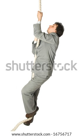 A man in a business suit climbing a rope