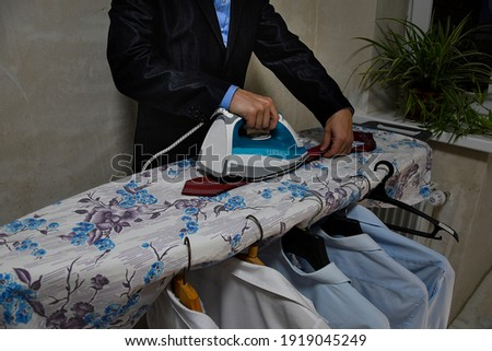 A man in a business suit is ironing clothes, a hot iron is in the hands of her husband. There are several ironed shirts on the ironing board. A man is ironing a white sweater.