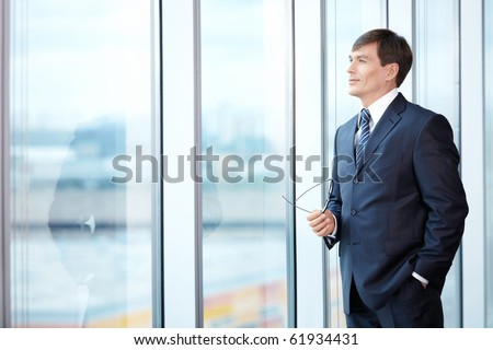 A man in a business suit looks out the window