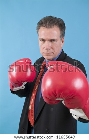 A man in a business suit with boxing gloves on, ready to punch the camera.