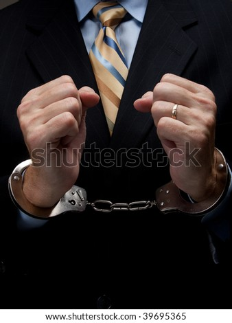 A man in a business suit with handcuffs