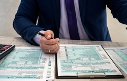 A man in a business suit writes a 1040 tax form in the office. Male hands fill on paper with calculator at workplace. Accounting concept