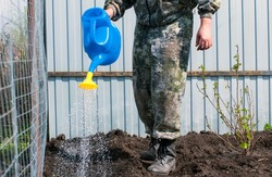 A man in a camouflage suit watering a garden from a blue watering can.