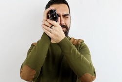A man in a casual shirt on a white background is shooting with an 8mm camera facing the camera. Vintage concept
