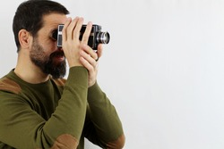 A man in a casual shirt on a white background is shooting with an 8mm camera turned sideways. Vintage concept