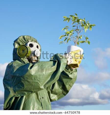 A man in a chemical suit and gas mask with a plant in the hands