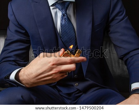 A man in a classic suit sits on a black leather sofa and shows off an expensive petrol lighter. Boss style. Nervous waiting. Criminal authority. Gold accessory. Italian couturier