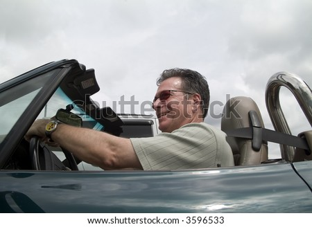 A man in a convertible sports car driving with the top down and passing a car.