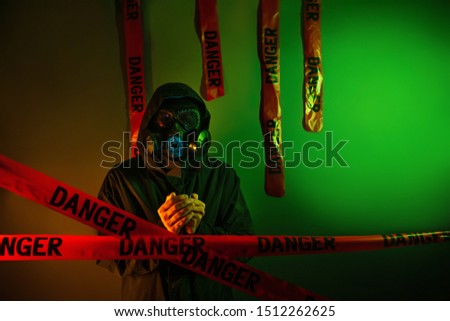 A man in a dark green protective suit with a gas mask on his face and a hood on his head posing standing near a green wall with hanging danger tapes