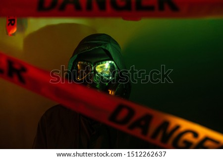 A man in a dark protective suit with a gas mask on his face and a hood on his head posing standing near a green wall with danger tapes