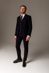 A man in a dark suit, white shirt, black boots and glasses is standing against a plain background, looking straight. Business clothes. Confident look. Success. Vertical photo