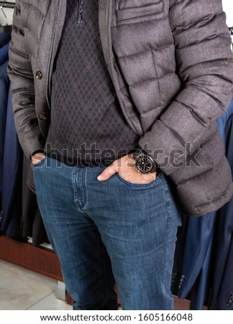 A man in a down jacket and jeans stands in the trading floor of a men's clothing store, hands in pockets. Against the background of clothes. Winter clothes season 2020