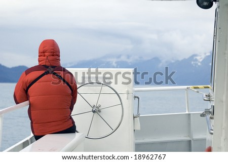 A man in a down parka sits on the bow of a day cruise boat in Alaska's Kenai National Park