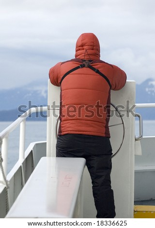 A man in a down parka stands on the bow of a day cruise boat in Alaska's Kenai National Park