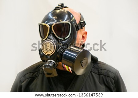 A man in a gas mask. A person with a respirator. Respiratory protection. Chemical protection. Filter mask. Personal protective equipment. Protective clothing in the chemical industry. #1356147539
